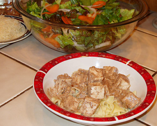 Pecan Cream Tofu on noodles with mixed greens, cheese, and chopped pecans